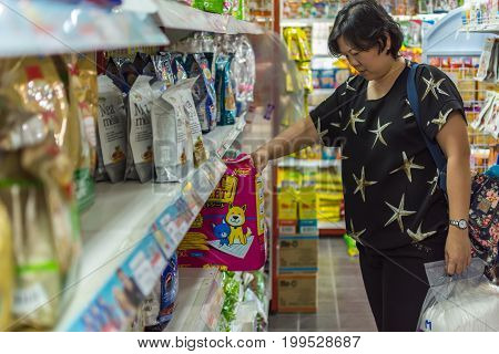 Woman Shopping Accessories Or Pet Food In Petshop