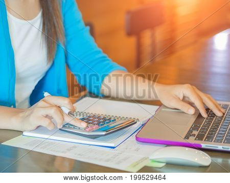 Closeup business woman hand using a calculator with laptop computer for online payment in cafe office. Business finance concept.