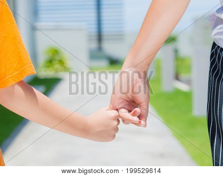 close up of woman holds the hand of a lovely child. Mother and son holding hands in the background of the green field. People charity and family concept.