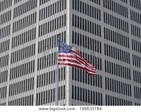 DETROIT - August 11, 2017. The flag of the United States flies on a tall flagpole at the corner of One Woodward Avenue, a 32 story downtown Detroit, Michigan office building, which is distinguished by tall, narrow windows.