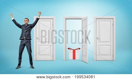 A happy businessman stands close to three doors where only one is open with a gift box inside. Best choice. Lottery winner. Luck and fortune.