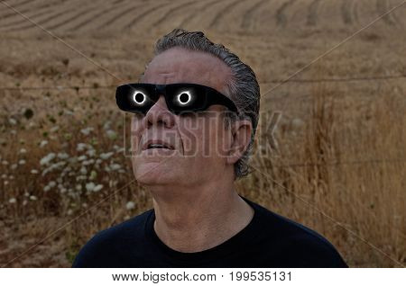 Man viewing full solar eclipse with solar glasses in country field