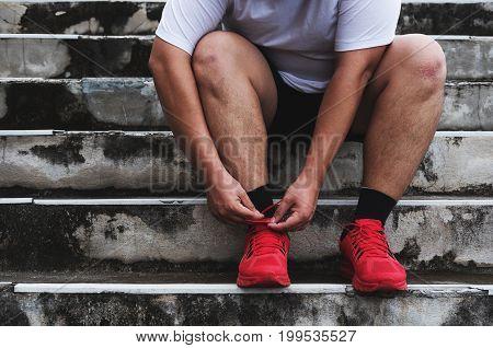 Asian Guy Tying Running Shoe, Preparing to Running for Losing Weight