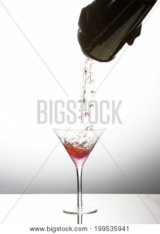 Pink cocktail being poured into martini glass