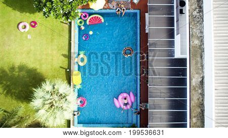 Aerial view of people enjoying the pool with inflatable tubes