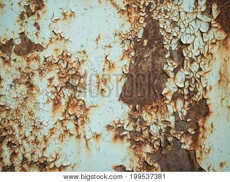 Texture of old rusty metal with streaks of rust and cracked, flaking paint. Surface of rusty metal close-up with old and faded paint.