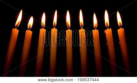 Selective focus on nine candles on a dark background.