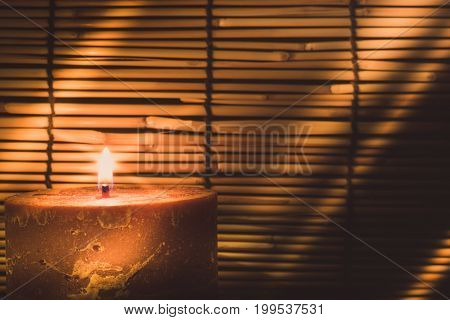 Candle Light On Blurred Old Wooden Background At The Night. Selective Focus On Tha Candle With Soft