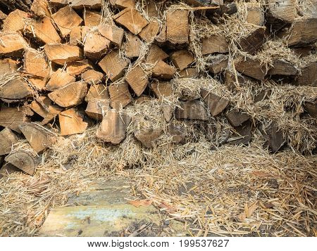 The fuel wood stacked on top of each other mixed with straw. Boards of pine, view of the end. Firewood for heating the house and kindling. Wood for the stove. Look at the stack of firewood close-up