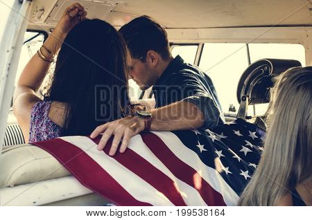 People Sitting in a Front Seat with American Flag on Rear Seat