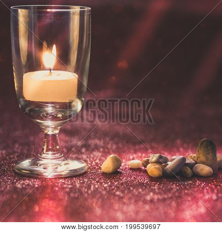 Golden light of candles burning in wine glass with light effect and red blurred bokeh background. Vintage image style.