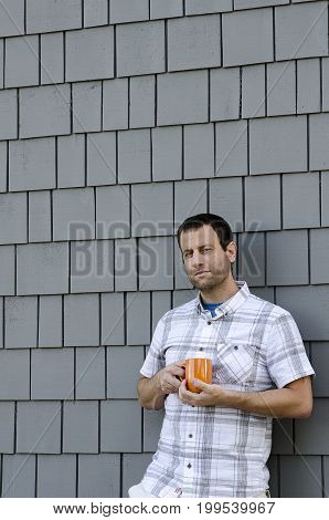 Man leaning against a gray wall holding an orange coffee mug outside.