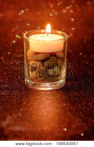 Golden Light Of Candles Burning In Cup Glass With Light Effect And Red Blurred Bokeh Background. Abs