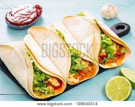 Three homemade tacos with chicken, vegetables and salsa. Latin food tacos on black wooden cutting board over blue wooden background