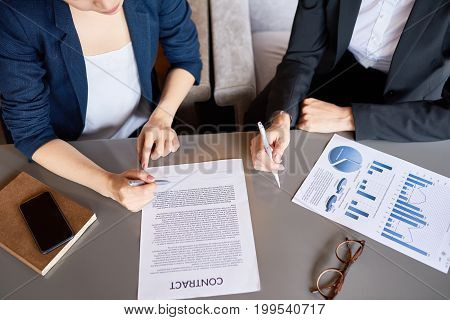High angle view of unrecognizable business partners signing contract while having productive negotiations in boardroom, close-up shot