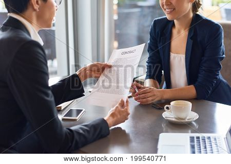 Unrecognizable white collar worker in eyeglasses reading contract with concentration before signing it, her business partner sitting opposite her at spacious cafe