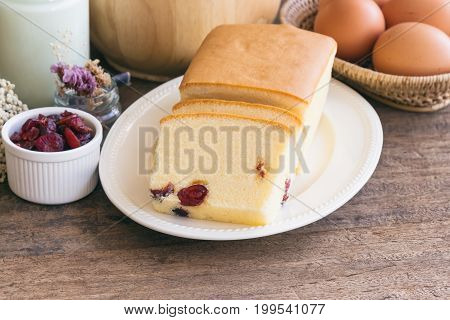 Slices of butter cake on white plate. Homemade butter cake with dried cranberries so delicious soft and moist. Tasty pound cake or butter cake served on wood table. Homemade bakery background concept. Piece of cranberries butter cake.