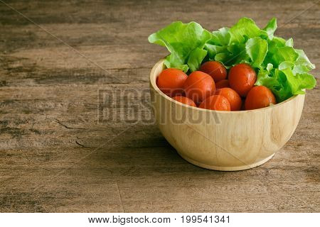 Fresh tomato and lettuce in wood bowl put on wood table. Side view of tomato and green oak lettuce with copy space for background. Fresh green oak lettuce and tomato prepare for cooking. Green lettuce and red tomato concept for background.