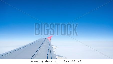 Wing of an airplane flying above the clouds. people looks at the sky from the window of the plane, using airtransport to travel.