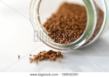 Instant coffee in the bottle on white background