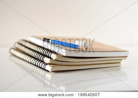 Stack of books pencil and eraser on white background