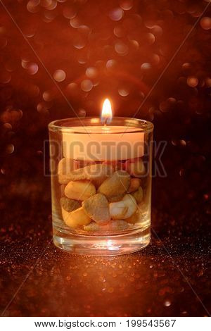 Golden light of candles burning in cup glass with light effect and red blurred bokeh background. abstract background for pray or meditation caption and hope concept.