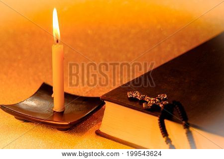 Still life golden candle light and Bible Book on golden blurred bokeh background. abstract background for pray or meditation caption.