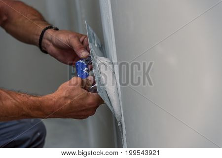 old manual worker with wall plastering tools renovating house. Plasterer renovating indoor walls and ceilings with float and plaster.