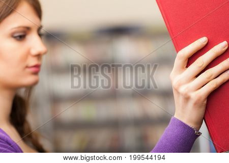 Portrait of a student taking a book from a bookshelf