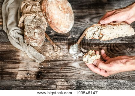 the preparation of bread, fresh delicious bread and hands with flour on the old wooden background, concept for baking
