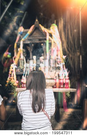 Thai people worship and pray on believe for success in life and good luck at ancient Thai outdoor spirit house shrine Thai style made from old wood. bangkok Thailand.
