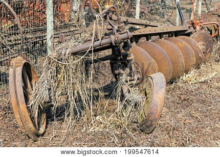 Close up of vintage rusted discarded agricultural plough covered in grass on farmstead