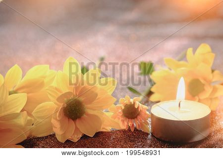 Prayer and hope concept. Retro candle light and yellow flower with lighting effect and glitter abstract background with bokeh defocused lights.