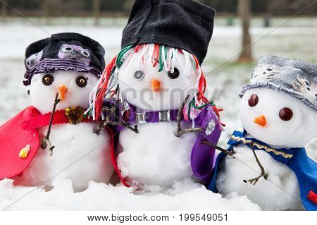 Three stylish snowmen dressed beautifully. Small and cute characters sat in a snow scene in winter during Christmas
