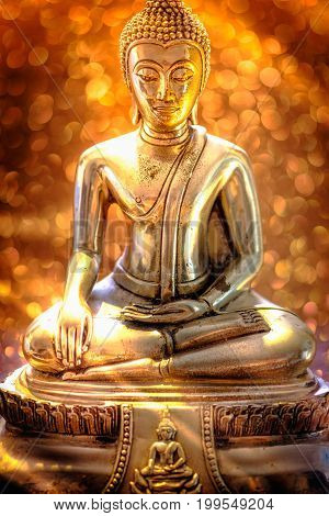 Selective focus of buddha statue with soft lighting effect and glitter abstract background with bokeh defocused lights. Concept of peace meditation hope and relaxation.