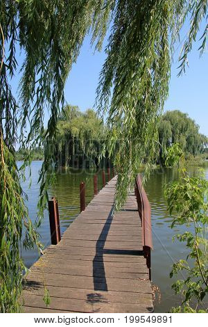 The picture was taken in Ukraine in Gaivoronsky district. In the picture a footbridge on a green island is located in the middle of a picturesque lake.