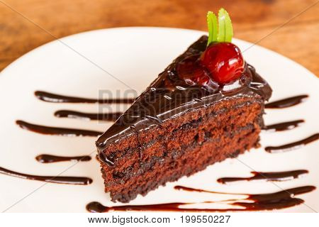 Chocolate cake with chocolate creame on white plate.