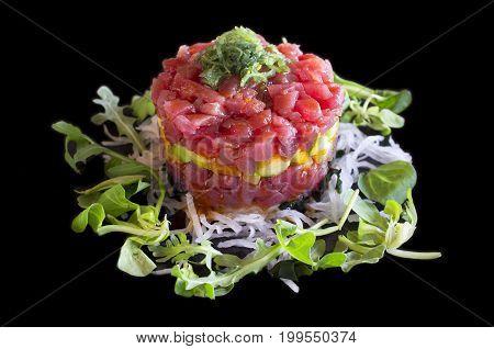 Black plated dish of Ahi Tuna Tartar. Isolated over black background