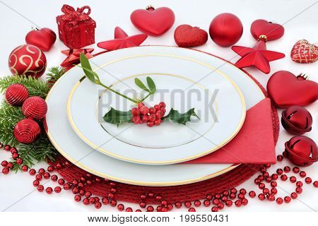 Christmas dinner table setting with porcelain plates, holly, mistletoe, fir and red bauble decorations on white background