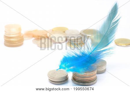 Close Up And Selective Focus On Blue Feather On Thai Coins Stack With White Background. Economy , Sa