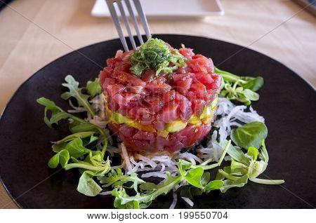 Black plated dish of Ahi Tuna Tartar with fork. Closeup