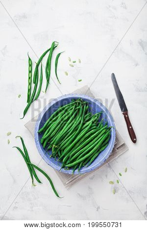 Crop of green or string beans in vintage bowl and knife on white stone background top view. Organic and diet food.
