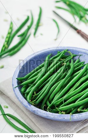 Harvest of green or string beans in rustic bowl on white table. Organic and diet food.