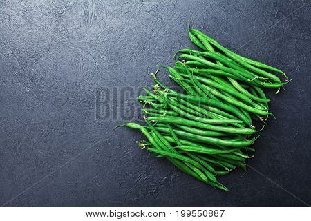 Young green or string beans on black stone table top view. Organic vegetarian food.
