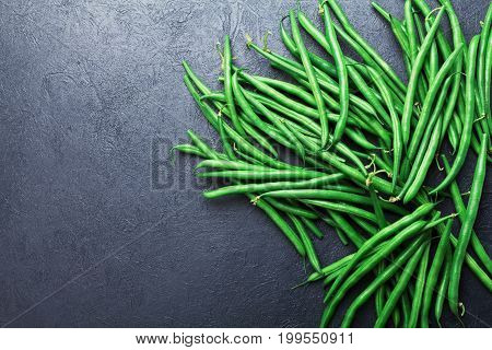 Heap of green or string beans on black stone table top view. Organic and diet food.