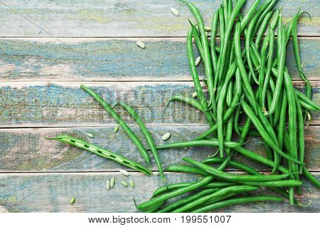 Heap of green or string beans on rustic table top view. Organic and diet food. Farmers autumn harvest.