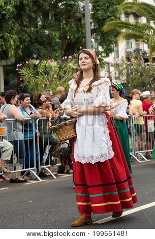 women in traditional costume carry the basket of grapes durnig historical and ethnographic parade of Madeira Wine Festival in Funchal. Madeira Portugall