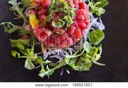 Black plated dish of Ahi Tuna Tartar. Closeup