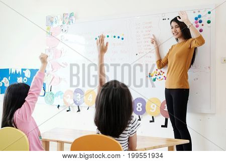 Young woman teacher teaching kids in kindergarten classroom preschool education concept