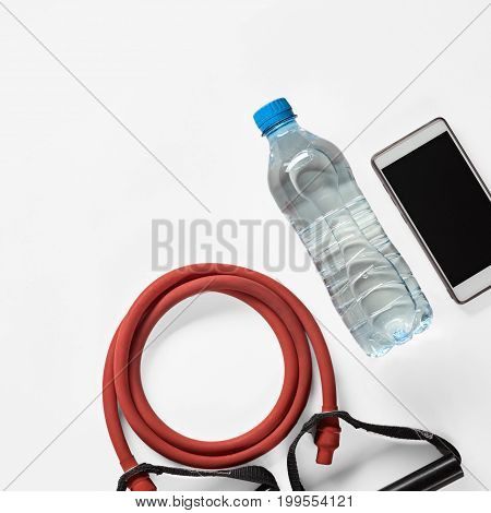 Modern fitness supplies smartphone, drinking water and expander, image with Square ratio